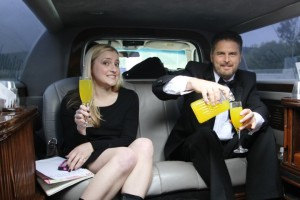 photo of people having a drink in the back of a limousine